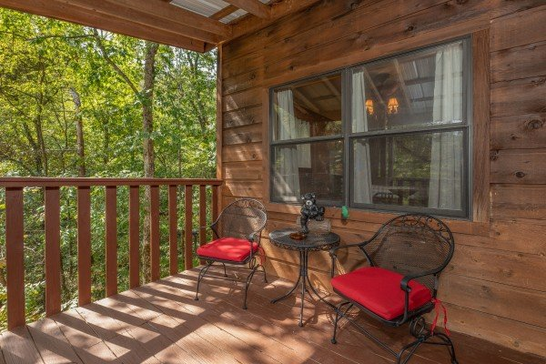 Bistro set on a covered deck at Misty Mountain Sunrise, a 3 bedroom cabin rental located in Pigeon Forge