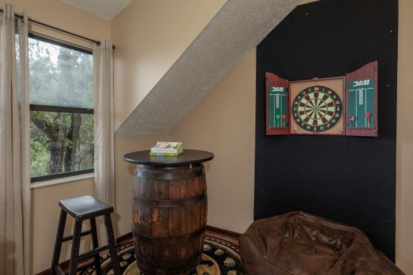 Dart board and pub table in the game loft at Misty Mountain Sunrise, a 3 bedroom cabin rental located in Pigeon Forge
