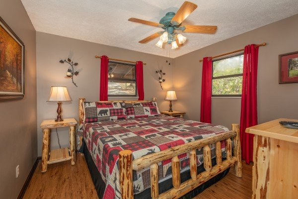 Bedroom with log bed, tables, lamps, and dresser at Misty Mountain Sunrise, a 3 bedroom cabin rental located in Pigeon Forge
