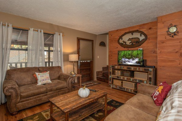 TV, sofa, and loveseat in the living room at Misty Mountain Sunrise, a 3 bedroom cabin rental located in Pigeon Forge