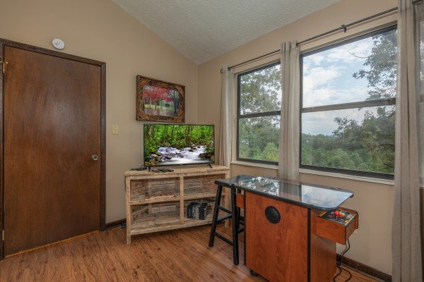 TV and arcade game in the game loft at Misty Mountain Sunrise, a 3 bedroom cabin rental located in Pigeon Forge