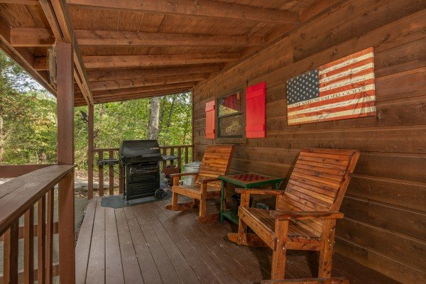 Gas grill and chairs on a covered deck at Misty Mountain Sunrise, a 3 bedroom cabin rental located in Pigeon Forge