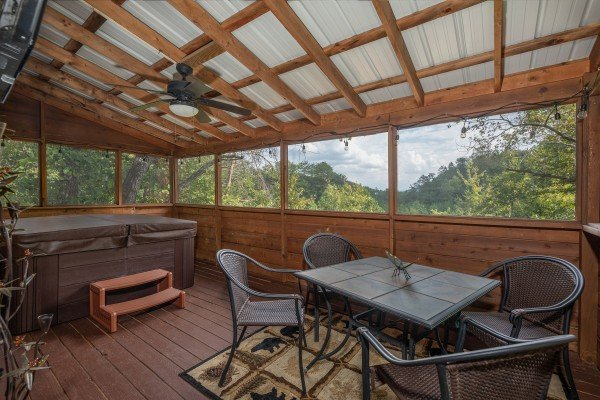 Screened in porch with dining space for four and a hot tub at Misty Mountain Sunrise, a 3 bedroom cabin rental located in Pigeon Forge