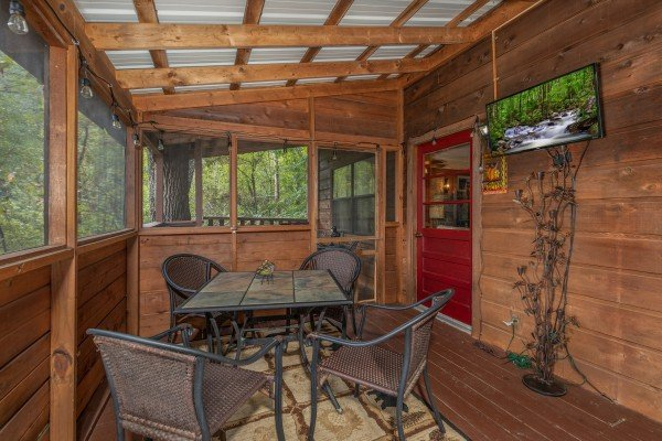 Screened in porch with dining space for four and a TV at Misty Mountain Sunrise, a 3 bedroom cabin rental located in Pigeon Forge