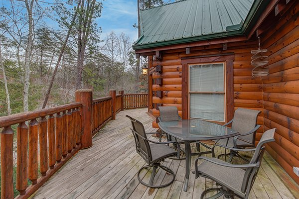 Deck dining for four at Smokies Paradise Lodge, a 5 bedroom cabin rental located in Pigeon Forge