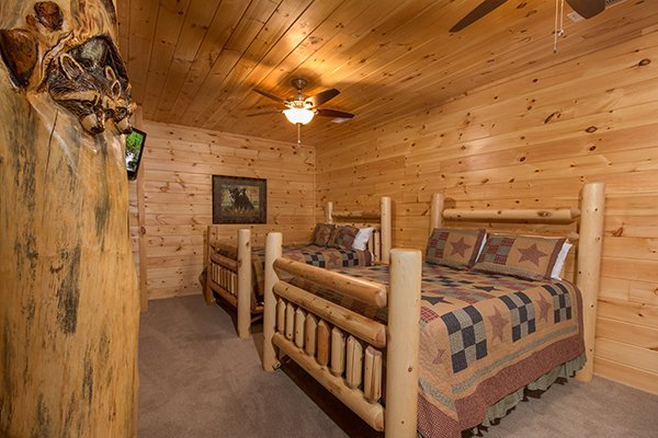 Bedroom with two log beds at Smokies Paradise Lodge, a 5 bedroom cabin rental located in Pigeon Forge