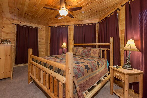 King log bed in a bedroom at Smokies Paradise Lodge, a 5 bedroom cabin rental located in Pigeon Forge