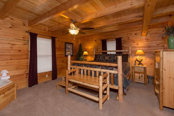 Bedroom with a log bed and bench at Smokies Paradise Lodge, a 5 bedroom cabin rental located in Pigeon Forge