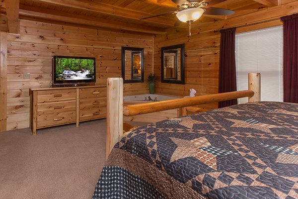 Dresser, TV, and jacuzzi in a bedroom at Smokies Paradise Lodge, a 5 bedroom cabin rental located in Pigeon Forge