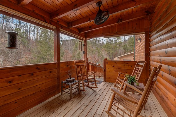 Covered deck with rocking chairs at Smokies Paradise Lodge, a 5 bedroom cabin rental located in Pigeon Forge