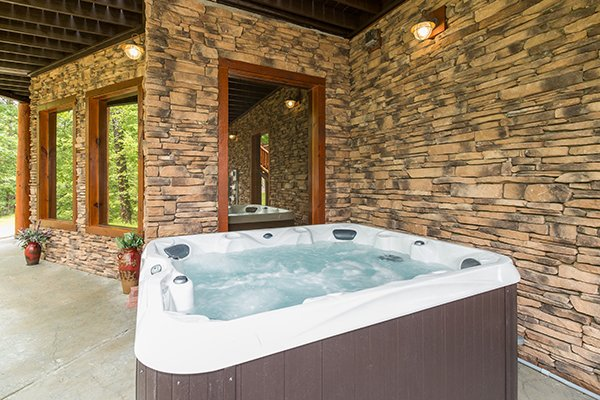 Hot tub on the patio at Smokies Paradise Lodge, a 5 bedroom cabin rental located in Pigeon Forge