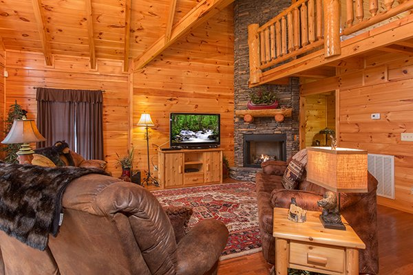 TV and fireplace in the living room at Smokies Paradise Lodge, a 5 bedroom cabin rental located in Pigeon Forge