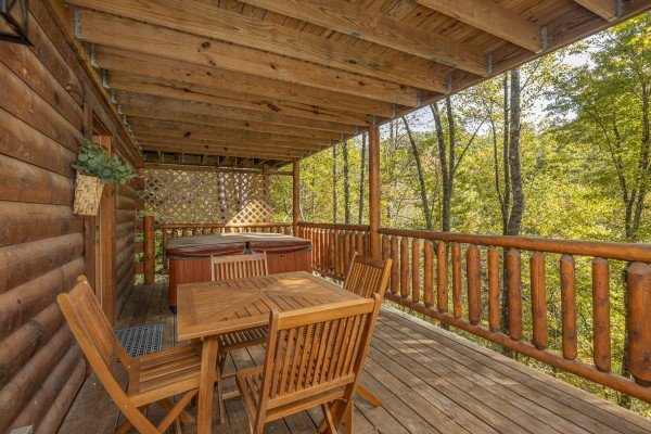 Dining for four on the deck at Silver Creek Cabin, a 1 bedroom cabin rental located in Pigeon Forge