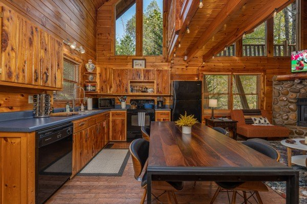 Dining table and kitchen with black appliances at Silver Creek Cabin, a 1 bedroom cabin rental located in Pigeon Forge