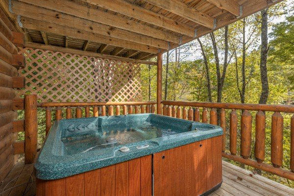 Hot tub on a covered deck at Silver Creek Cabin, a 1 bedroom cabin rental located in Pigeon Forge