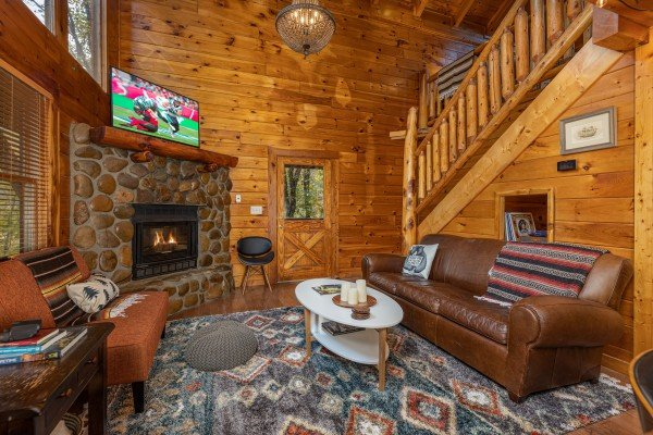 Living room with fireplace, TV, and sofa at Silver Creek Cabin, a 1 bedroom cabin rental located in Pigeon Forge