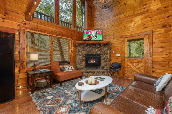 Living room with fireplace and TV at Silver Creek Cabin, a 1 bedroom cabin rental located in Pigeon Forge
